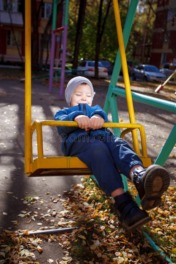 Happy boy playing in the autumn park, funny 4 years old toddler, seasonal walking outdoor, bright color of the weather, sunny day.  royalty free stock photos