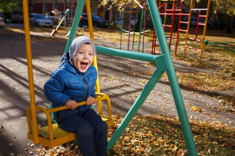 Happy boy playing in the autumn park, funny 4 years old toddler, seasonal walking outdoor, bright color of the weather, sunny day.  royalty free stock photography