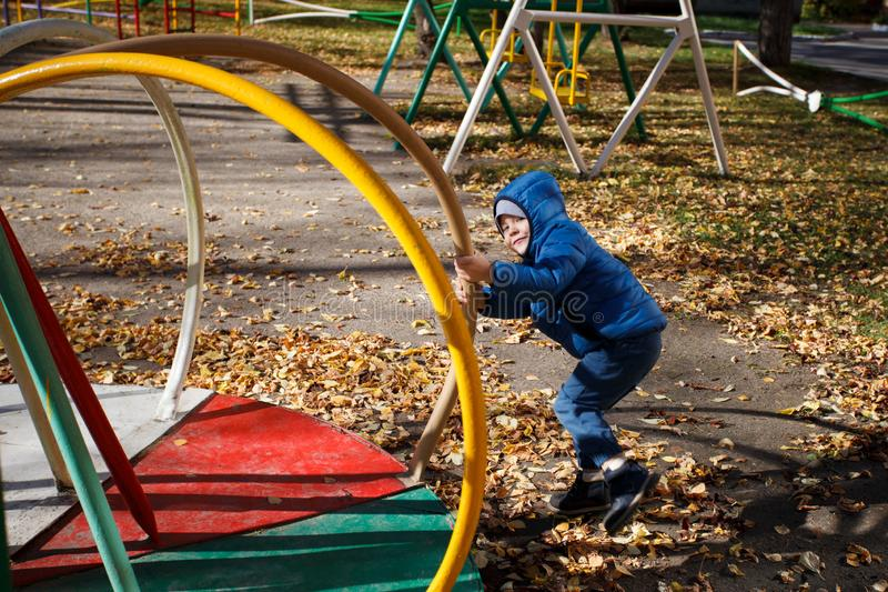 Happy boy playing in the autumn park, funny 4 years old toddler, seasonal walking outdoor, bright color of the weather, sunny day.  stock photo