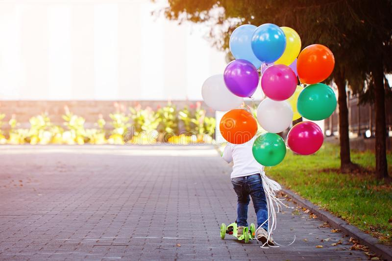 Happy boy playing with a bunch of balloons outside and riding a scooter. Back view royalty free stock photos