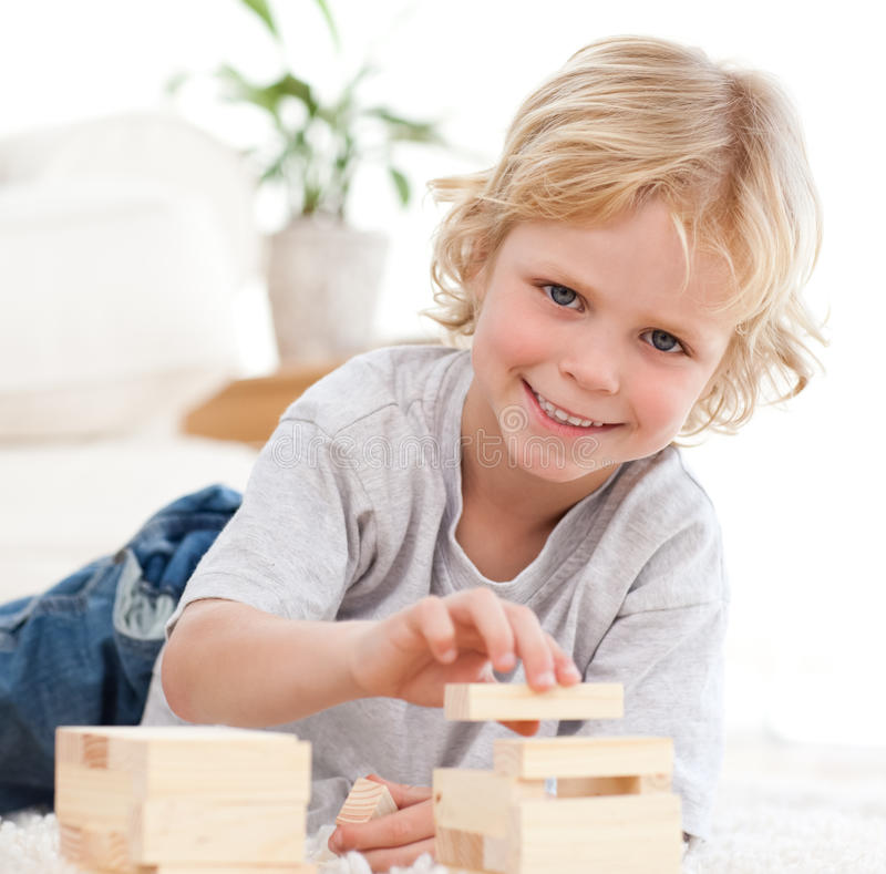 Happy Boy Playing With Dominoes Lying On The Floor Stock Photos