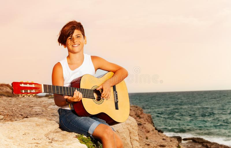 Happy boy playing guitar on the edge of a cliff stock photo