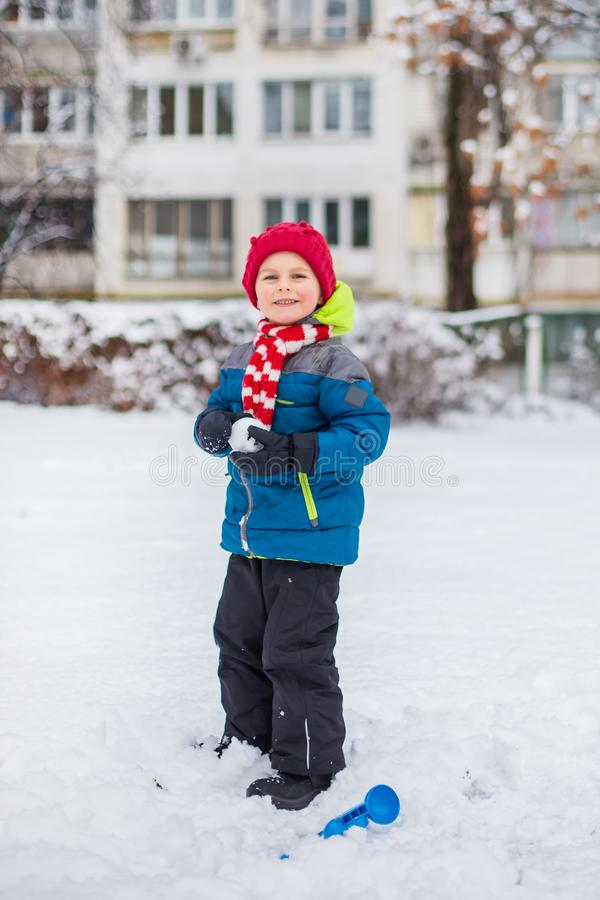Happy boy playing with snow on a snowy winter walk, making snowballs in the park royalty free stock photos