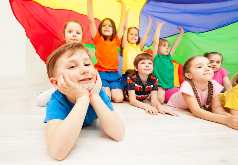 Happy boy playing under parachute with friends stock photos