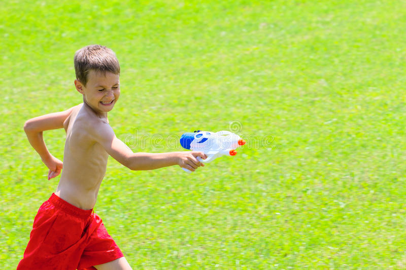 Happy boy playing with water gun at summer day royalty free stock image