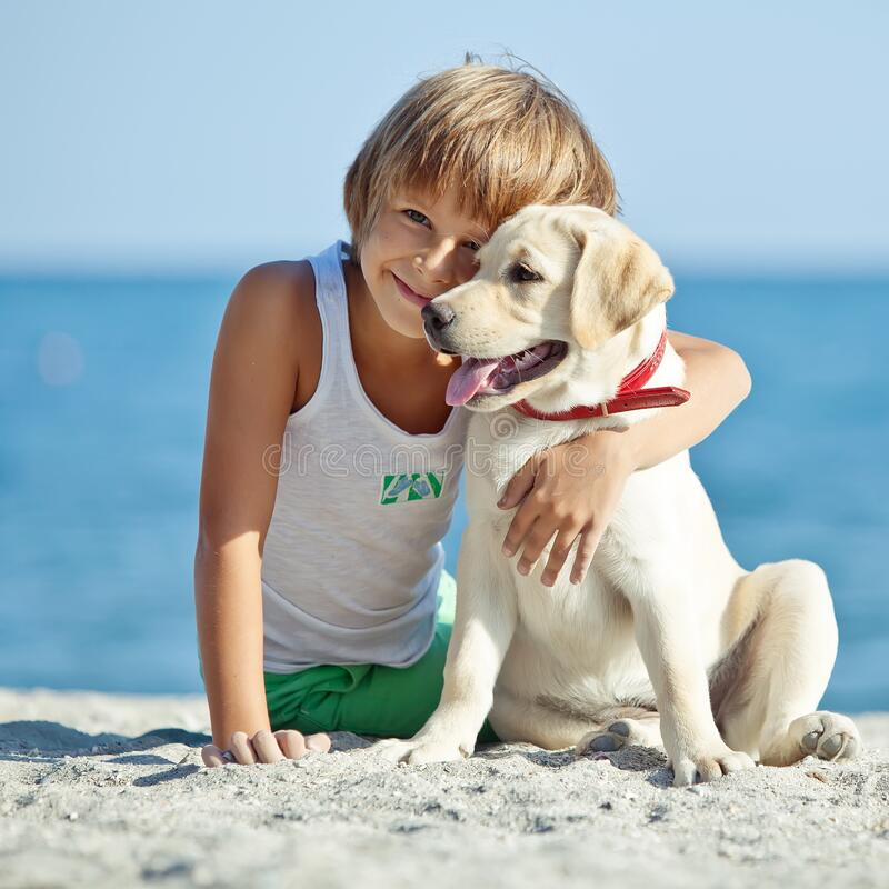 Free Happy Boy Playing With His Dog On The Seashore Against The Blue Sky. Best Friends Have Fun On Vacation. Royalty Free Stock Image - 199012046