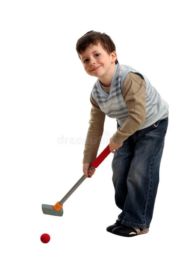 Happy boy preparing to hit a golf ball royalty free stock photo