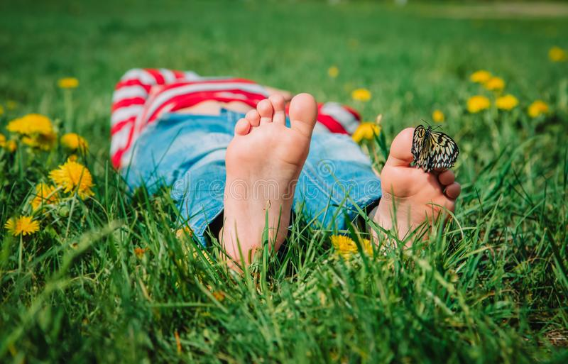 Boy relaxed on green grass, butterfly sitting on his feet in nature stock images