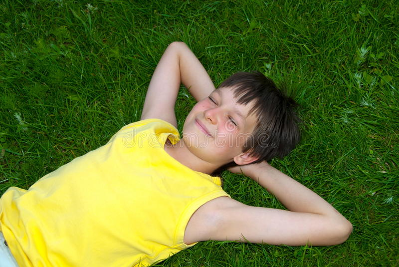 Happy boy resting on grass. A happy teen boy resting on green grass stock image