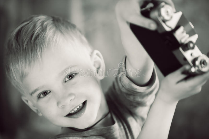 Happy boy with retro camera in hands royalty free stock images
