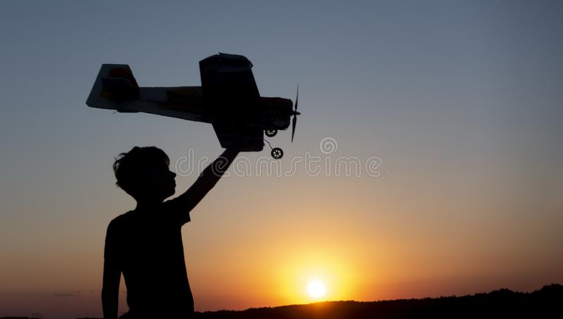Happy Boy runs with a toy airplane on a field in the sunset light. Children play toy airplane. teenager dreams of flying and. Happy Boy runs with a toy airplane stock photography