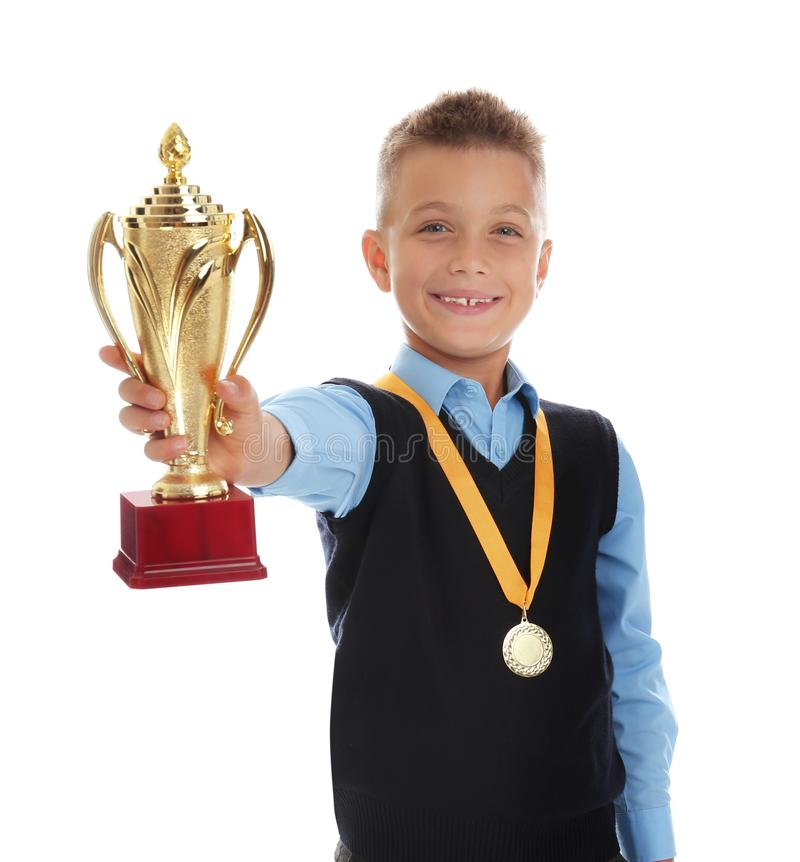 Happy boy in school  with golden winning cup and medal on white. Happy boy in school uniform with golden winning cup and medal isolated on white royalty free stock photo