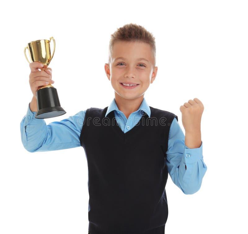 Happy boy in school uniform with golden winning cup on white. Happy boy in school uniform with golden winning cup isolated on white royalty free stock images