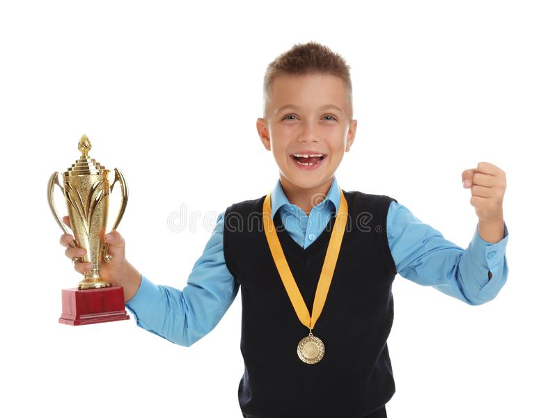 Happy boy in school uniform with golden winning cup and medal on white. Happy boy in school uniform with golden winning cup and medal isolated on white stock photography