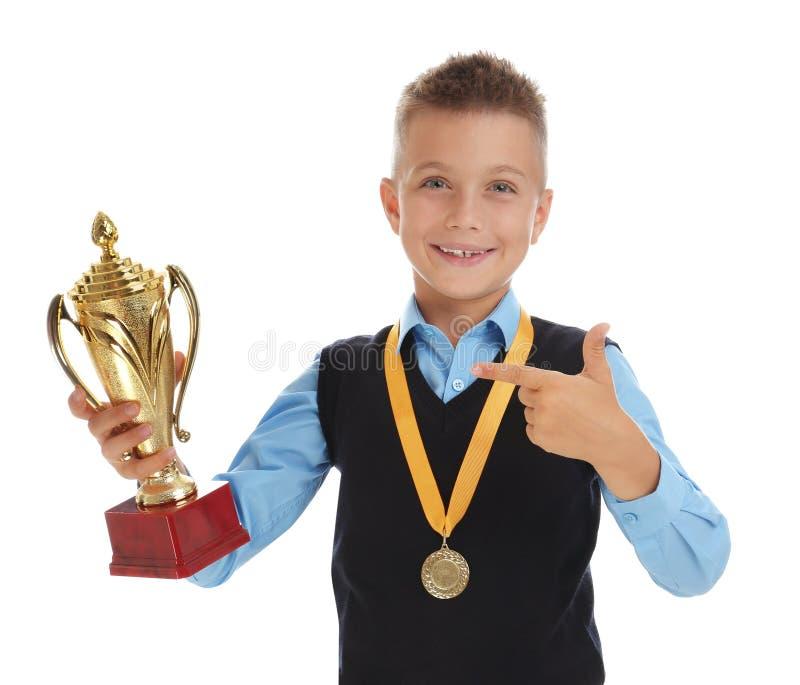 Happy boy in school uniform with golden winning cup and medal on white. Happy boy in school uniform with golden winning cup and medal isolated on white stock photos
