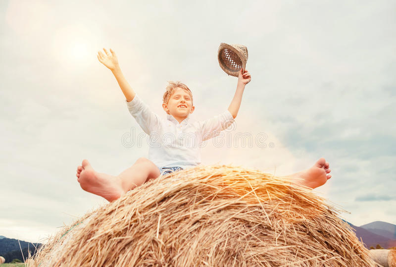 Happy boy sits over big rolling haystack royalty free stock photo