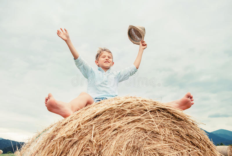 Happy boy sits over big rolling haystack royalty free stock images