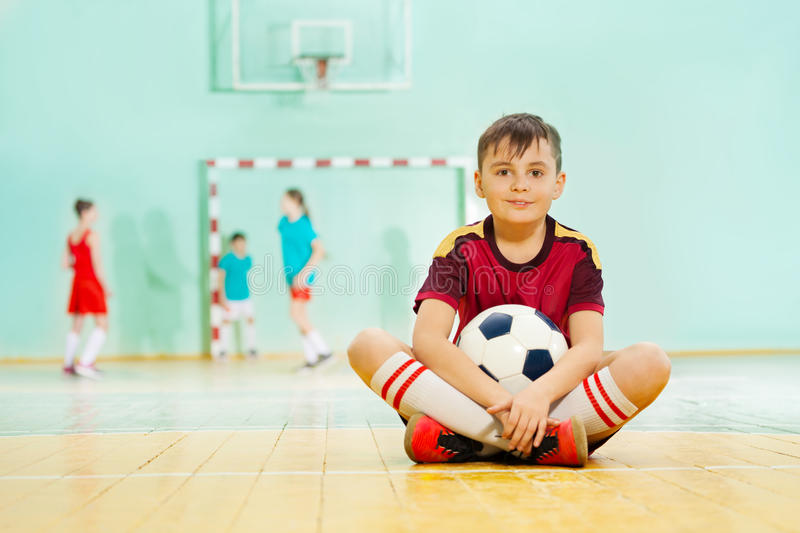 Happy boy sitting on the floor with soccer ball royalty free stock images