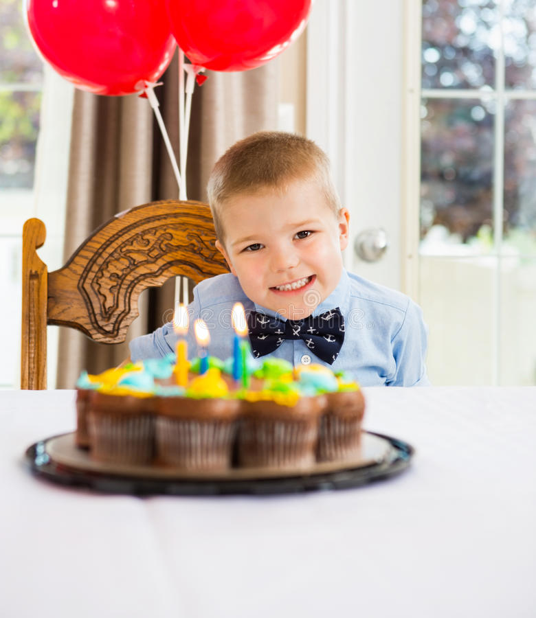 Happy Boy Sitting In Front Of Birthday Cake. Portrait of happy boy sitting in front of birthday cake at home stock photography
