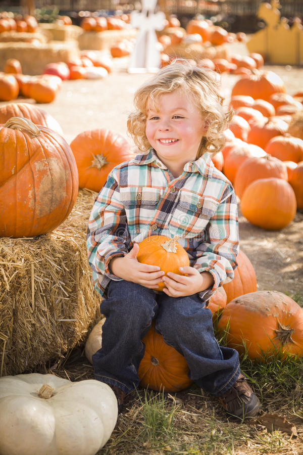Happy Boy Sitting and Holding His Pumpkin at Pumpkin Patch royalty free stock images