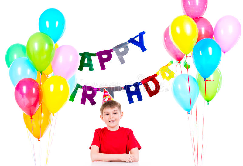 Happy boy sitting at the table in a birthday party. stock photos