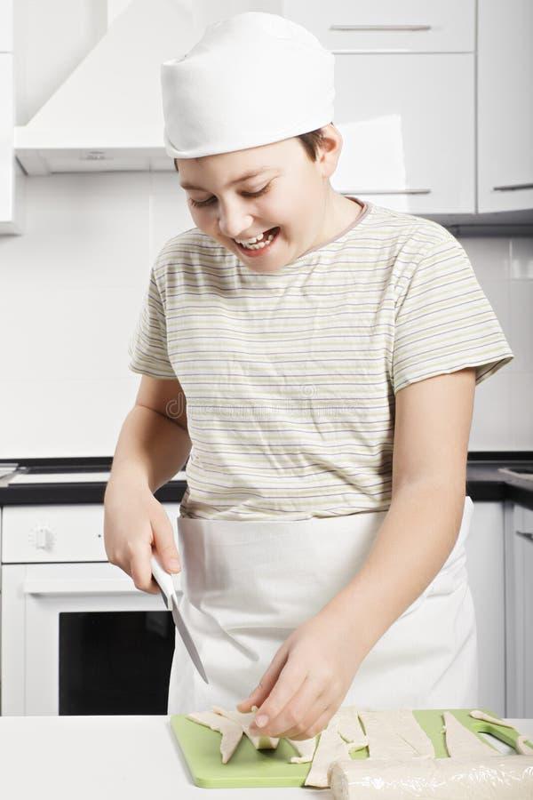 Happy boy slicing dough royalty free stock photos