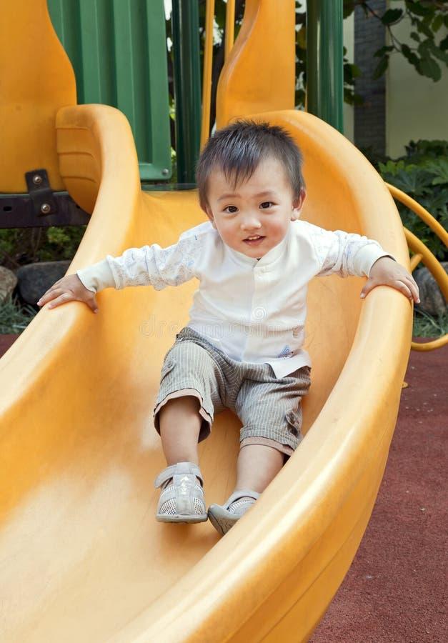 Happy boy sliding down slide stock image