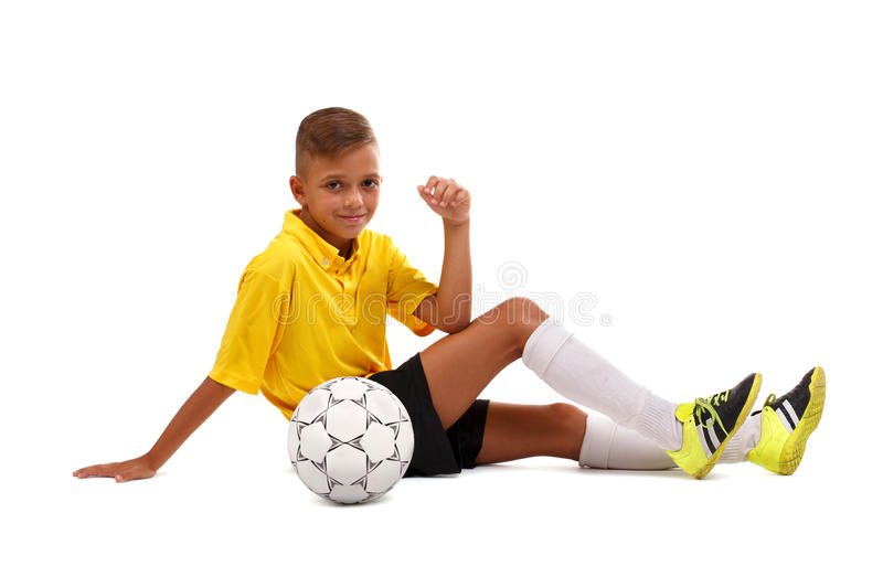 A happy boy with a soccer ball. A cheerful child in a football uniform isolated on a white background. Sports concept. royalty free stock photography