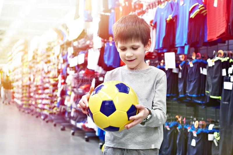 Happy boy with soccer ball in sport store royalty free stock images