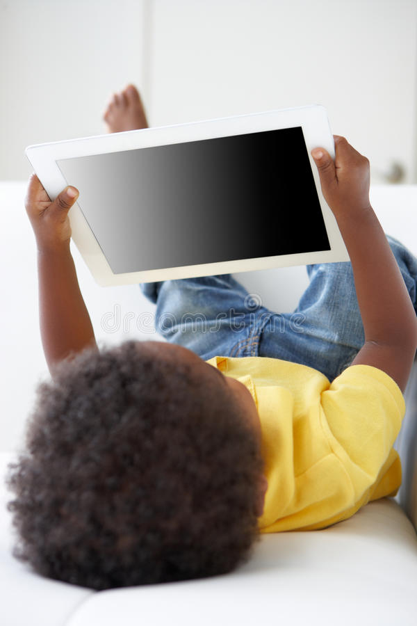 Happy Boy On Sofa Playing With Digital Tablet stock photography