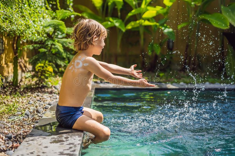 Happy boy with sun painted by sun cream on shoulder playing by the pool. Summer vacation concept. Space for text stock photos