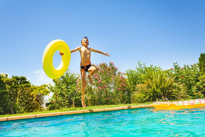 Happy boy with swim ring jumping in swimming pool. Portrait of teenage boy with big swim ring jumping in outdoor swimming pool at sunny day stock photos