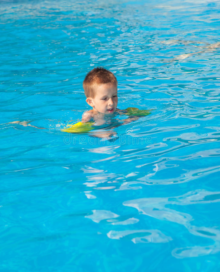 Happy boy swimming with floaties royalty free stock photos