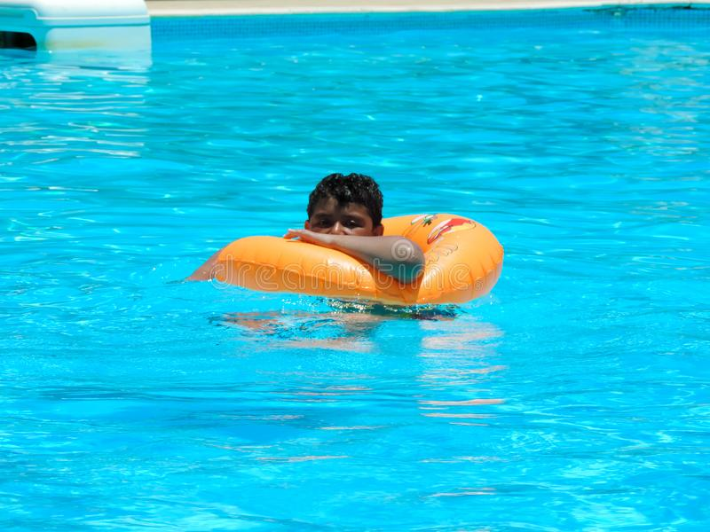Boy at swimming pool. Happy boy swimming at pool stock photography