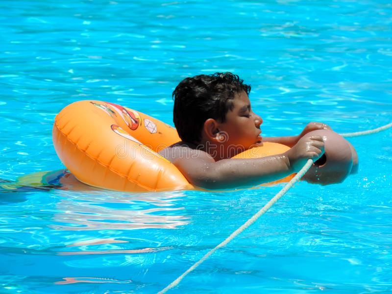 Boy at swimming pool. Happy boy swimming at pool stock image