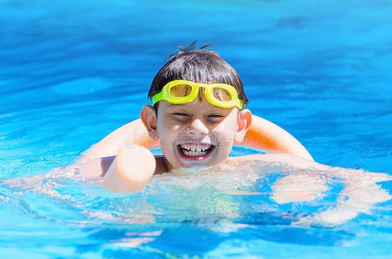 Happy boy on the swimming pool, summertime. stock photography