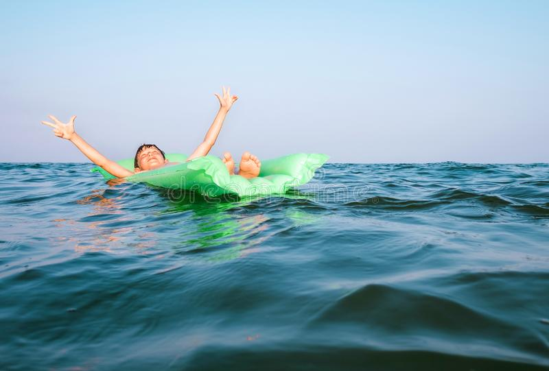 Happy boy swims on green inflatable mattress royalty free stock photos