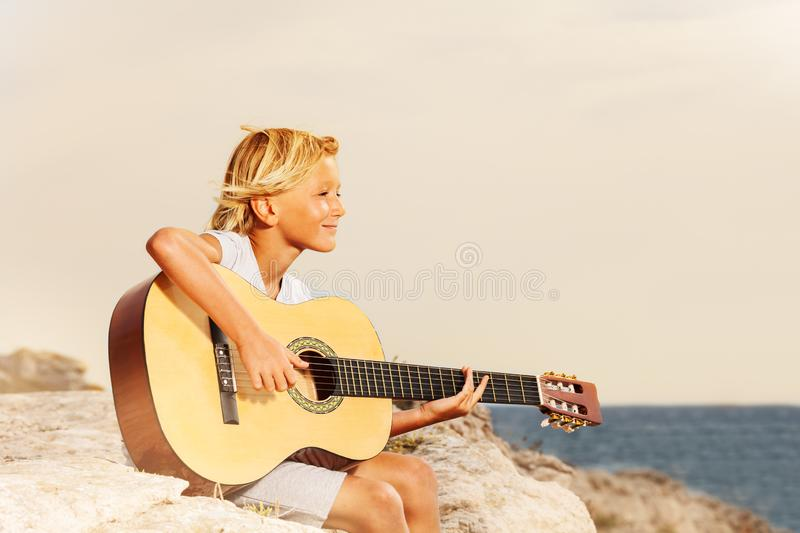 Happy boy teenager playing guitar at the seaside royalty free stock photography