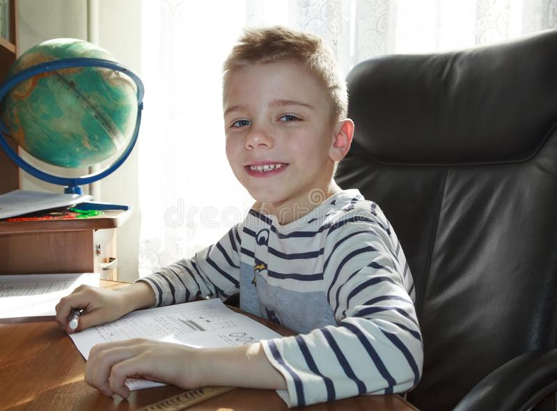 Happy boy thinks over the lessons and looks at the camera with a smile. Homework, doing, kid, child, little, alone, people, person, caucasian, childhood royalty free stock photo