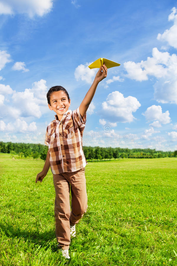 Happy boy throwing paper plane. Running in the park on sunny day royalty free stock photo