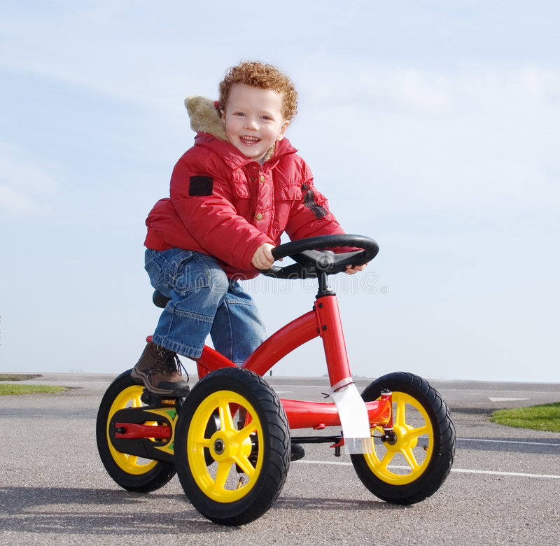 Happy boy on trike, bike. Happy preschool boy (3) riding on a red tricycle on a sunny winter day stock images