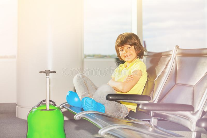 Happy boy waiting for boarding sitting at airport royalty free stock photography