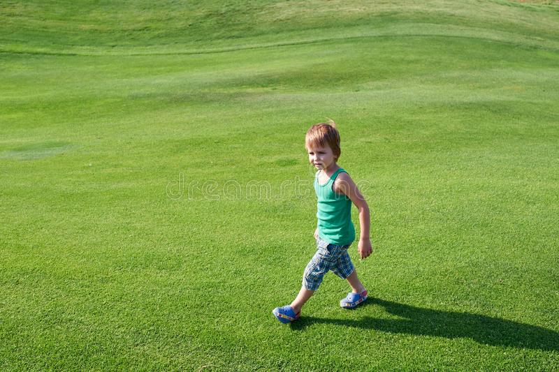 Happy boy walking the green golf course at sunny day royalty free stock photo