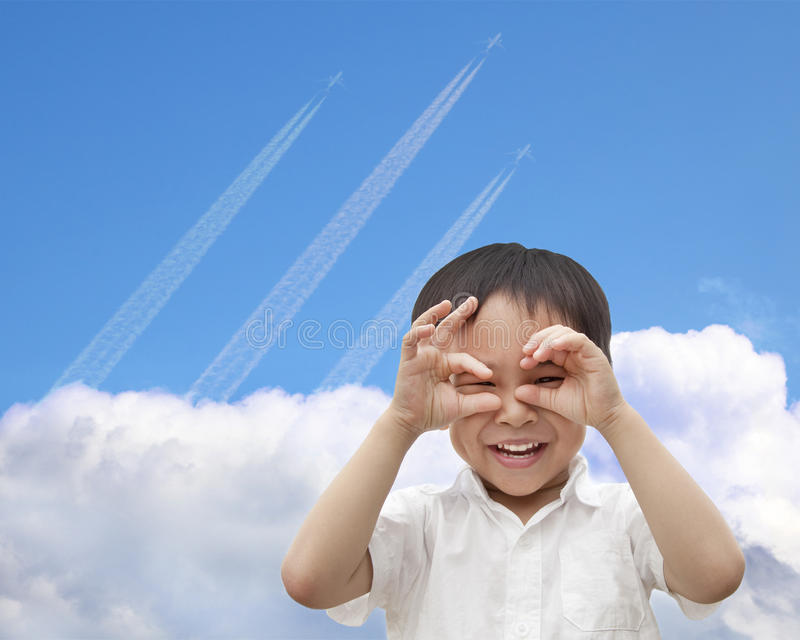 Happy boy watching airplane flying. Through the sky over the cloud royalty free stock photo