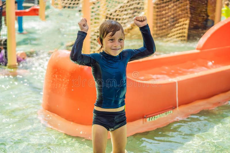 Happy boy on water slide in a swimming pool having fun during summer vacation in a beautiful tropical resort stock photography