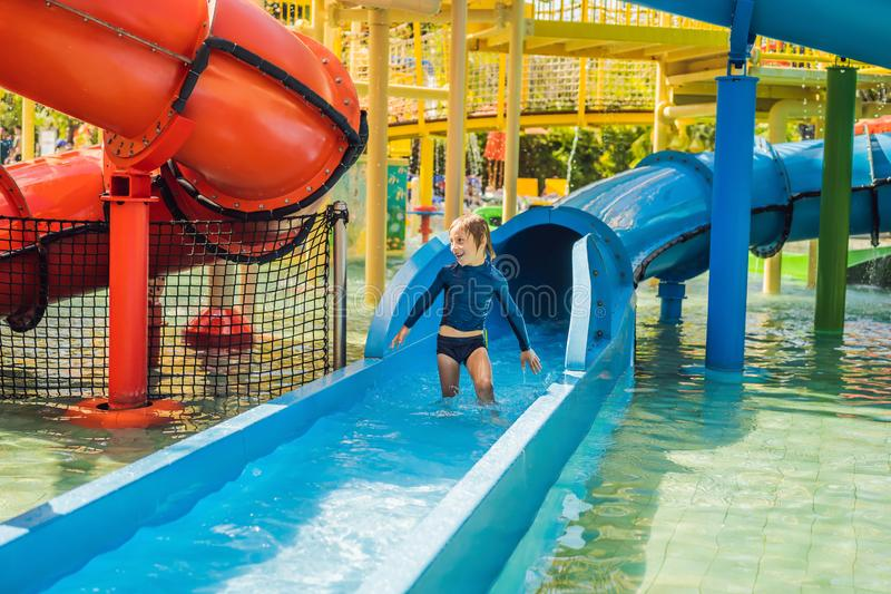 Happy boy on water slide in a swimming pool having fun during summer vacation in a beautiful tropical resort royalty free stock image