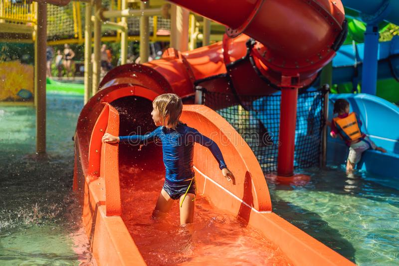 Happy boy on water slide in a swimming pool having fun during summer vacation in a beautiful tropical resort stock images