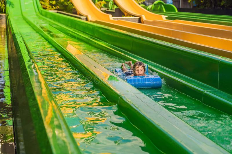 Happy boy on water slide in a swimming pool having fun during summer vacation in a beautiful tropical resort royalty free stock photos