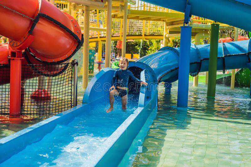 Happy boy on water slide in a swimming pool having fun during summer vacation in a beautiful tropical resort royalty free stock images