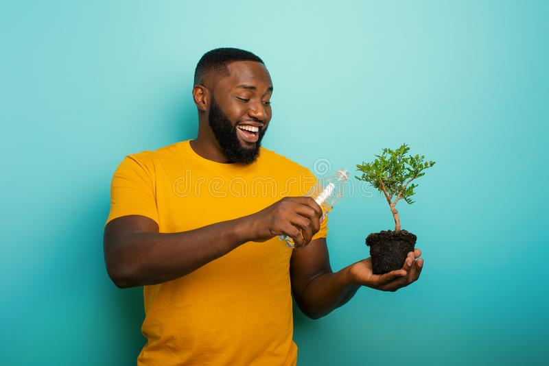 Happy boy watering a small tree ready to be planted. Concept of forestation. Happy black boy watering a small tree ready to be planted. Concept of forestation royalty free stock photography